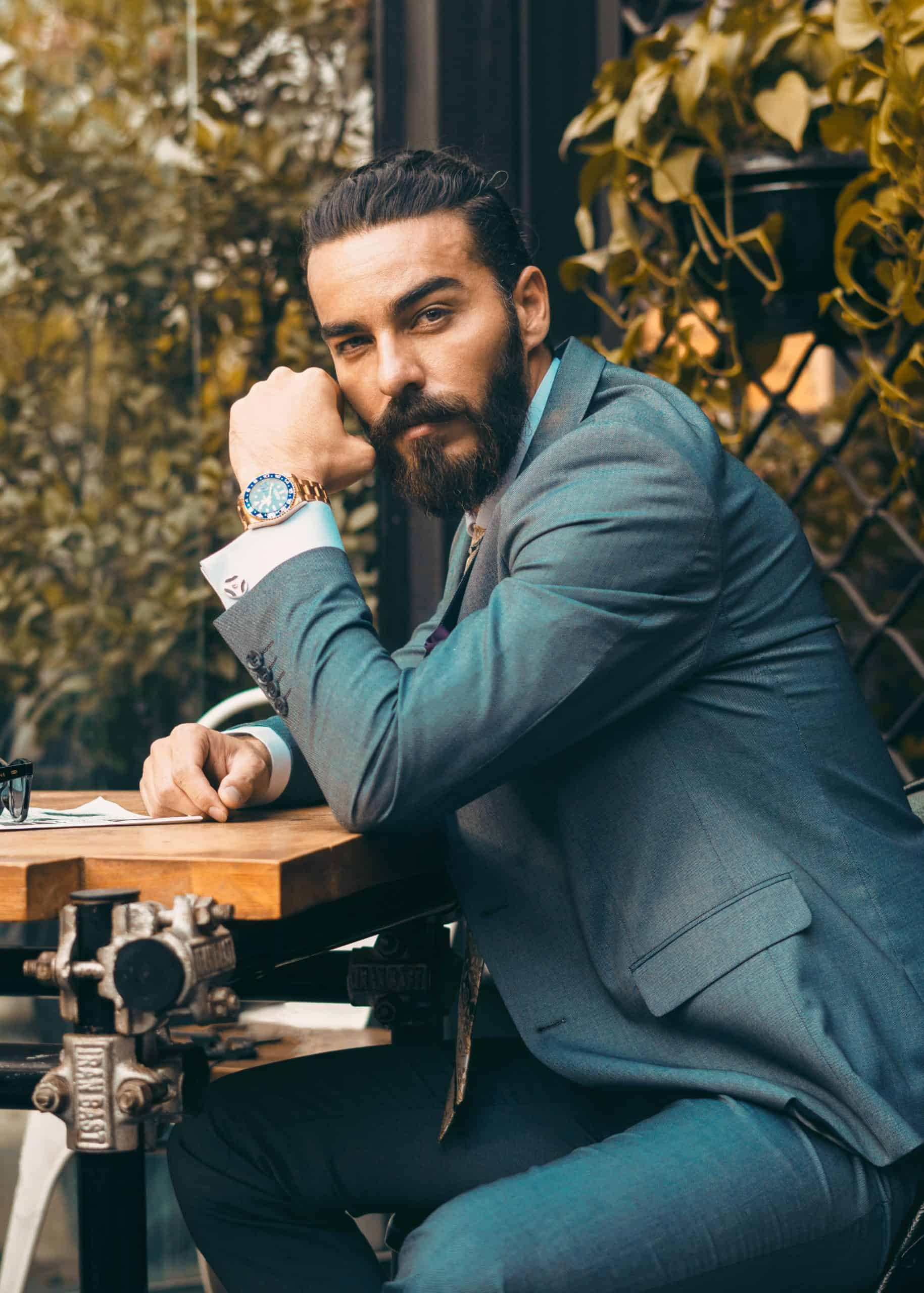 bearded man in suit displaying rolex