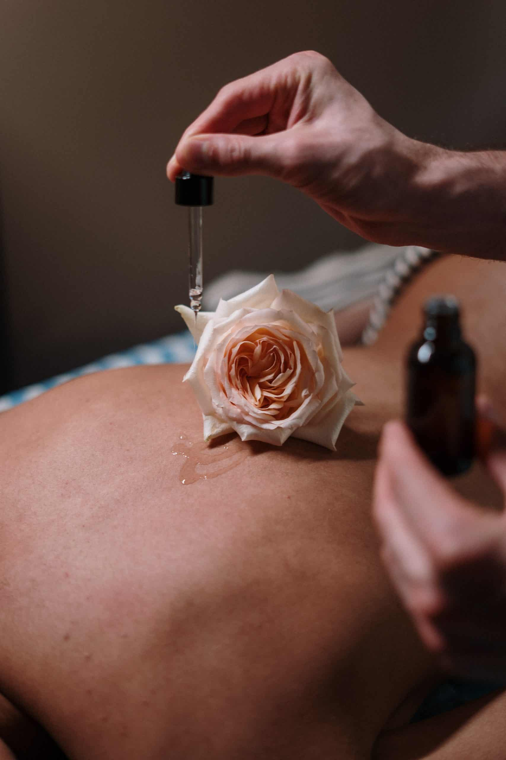 rose placed on the back whilst dropping oil onto skin
