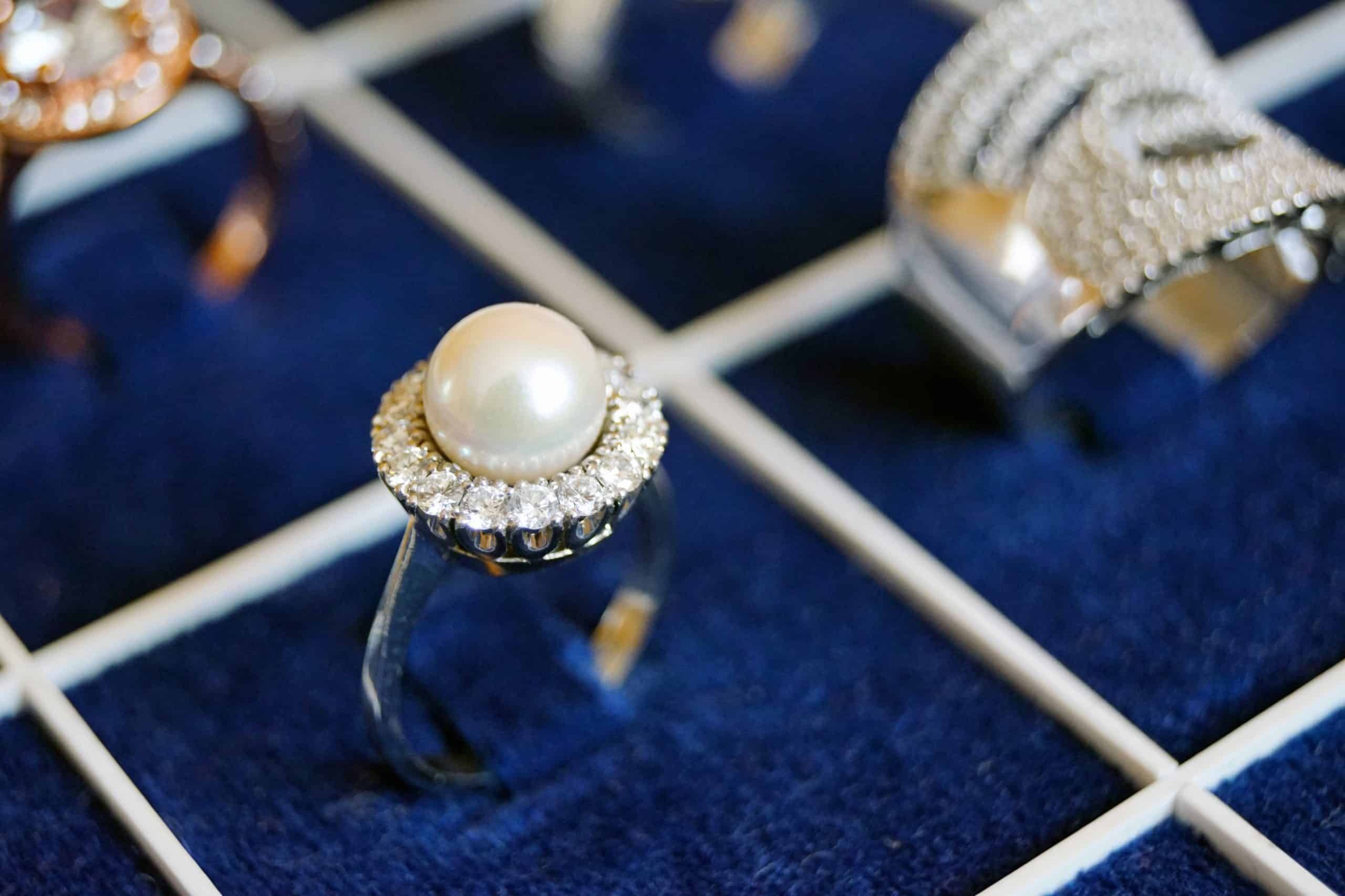 pearl ring with diamond borders on blue surface