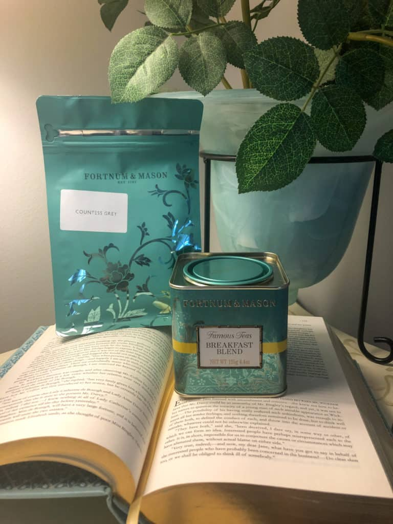 fortnum and mason teas standing on open book