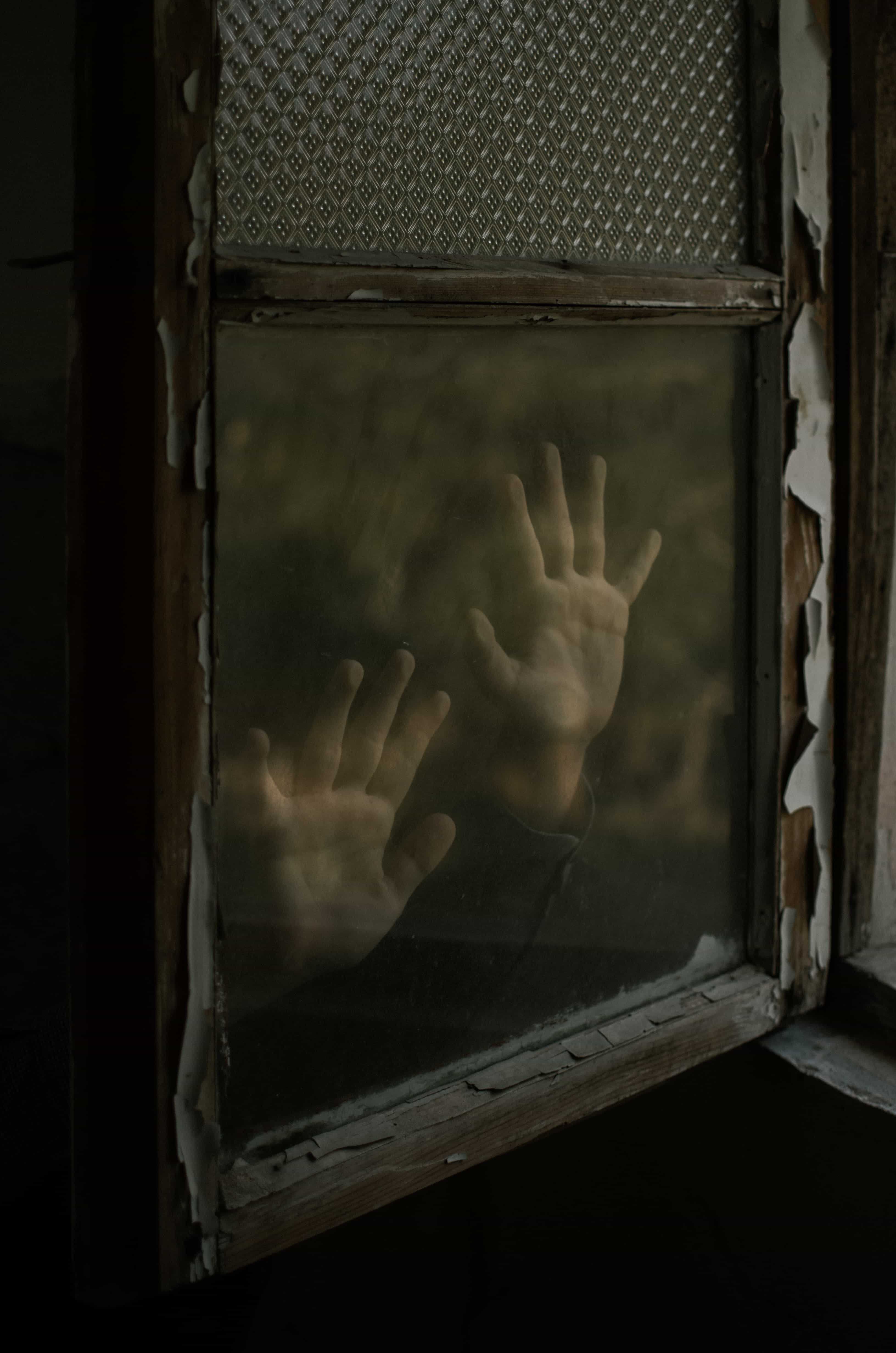 imprinted hands on old window pane