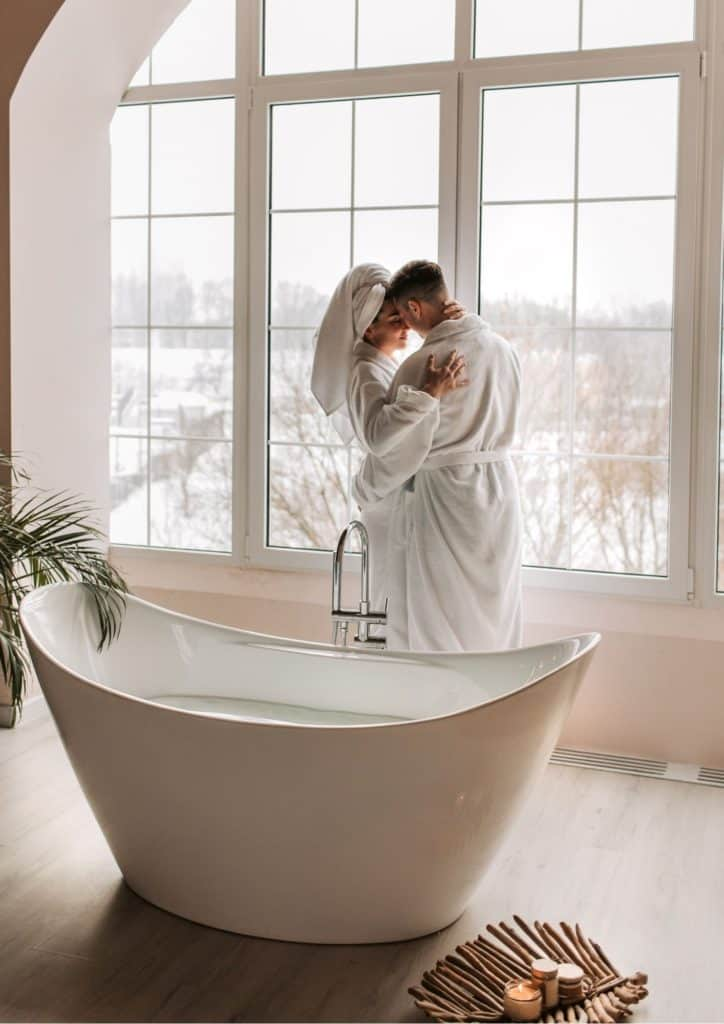 romantic couple in bathrobes by the window